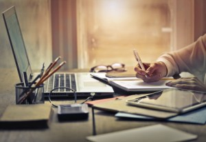 desktop with laptop, papers and hand holding pen
