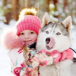 girl hugging Huskies in winter forest