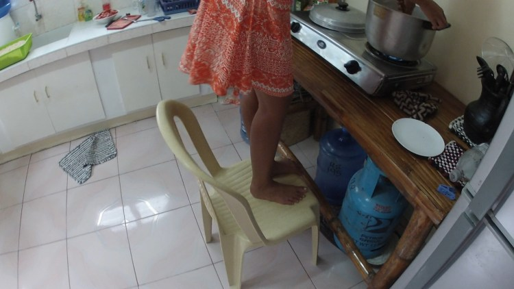 Michell stands on a chair to stir the sauce....