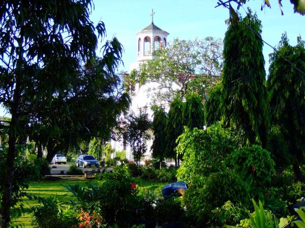 Arevalo Church through plaza greenery.