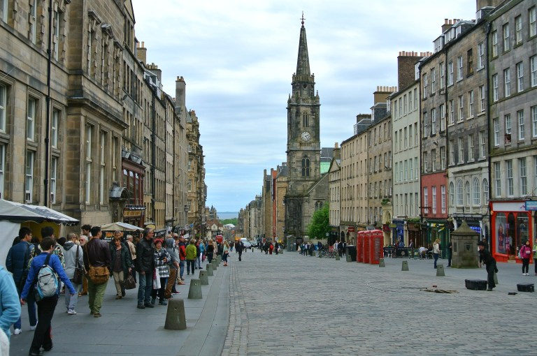 The Tron Kirk, red telephone boxes, and people on the Royal Mile in Edinburgh, Scotland.