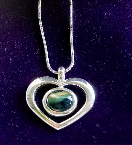 A green and blue Heathergem in a silver necklace.