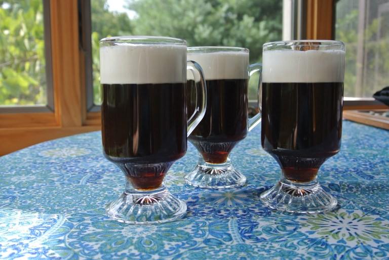 Three glasses of Prince Charlie's Coffee on a blue floral tablecloth.
