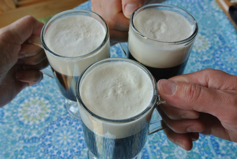 Three glasses of Prince Charlie's Coffee being clinked together in a toast.