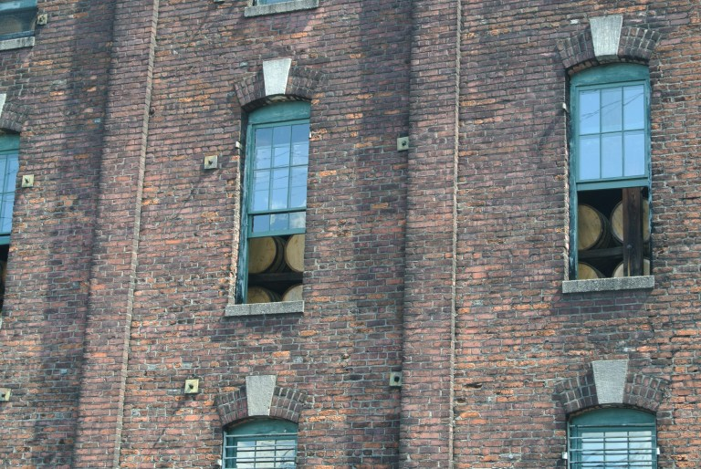 Whiskey barrels in the window of a brick warehouse.
