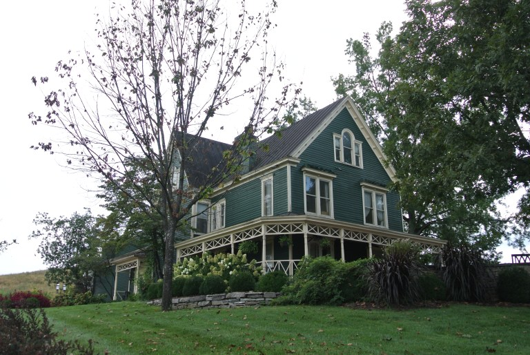 A green house with a wrap around porch.