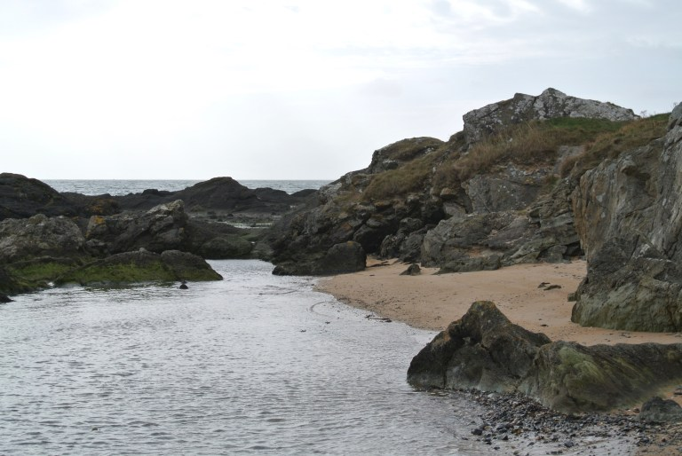 Dark, rugged rocks along a brown sandy beach.