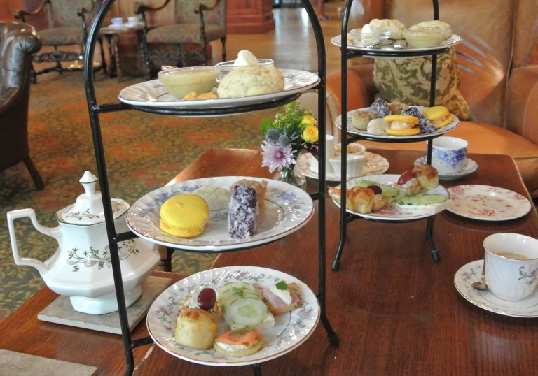 A teapot, teacups, and tiered trays of food at the O'Henry Hotel.