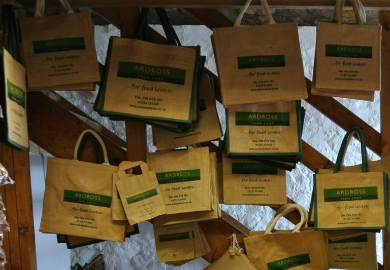 Reusable burlap bags hanging on hooks.