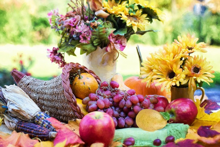 A cornucopia and jars filled with fall flowers.