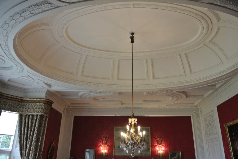 A carved white ceiling and a chandelier.