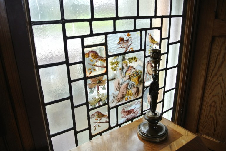 A stained glass window and a candlestick.