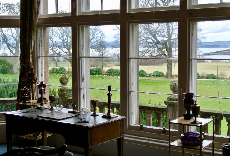 A desk sitting in front of a large window with views of the Firth of Forth.