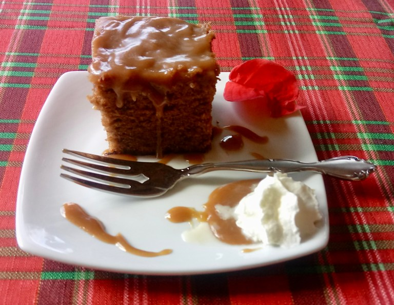 A slice of sticky toffee pudding on a Christmas tablecloth.