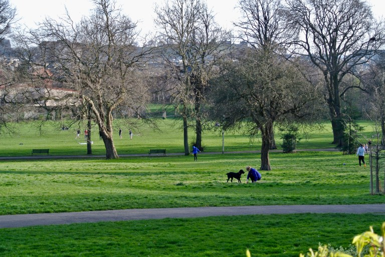 A lady with her black dog in Pilrig Park.
