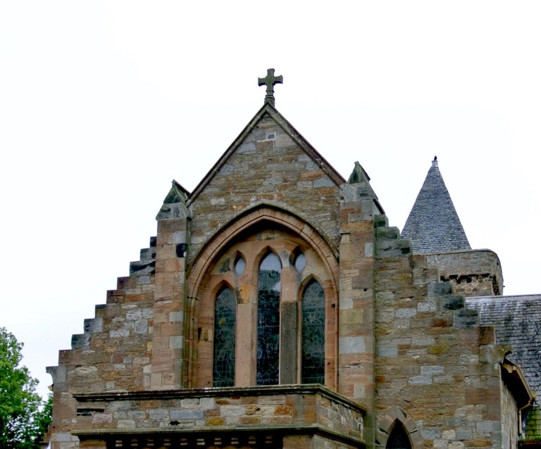 Upper window and a cross on the roof of Aberlady Parish Church.