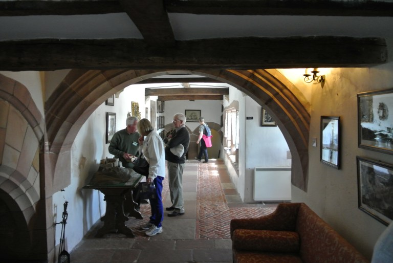 People standing just beyond an arch in a hallway at Lindisfarne Castle.