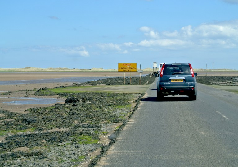 A blue car on the causeway.