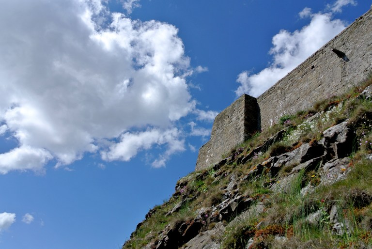 Fluffy white clouds and blue sky above Lindisfarne Castle.