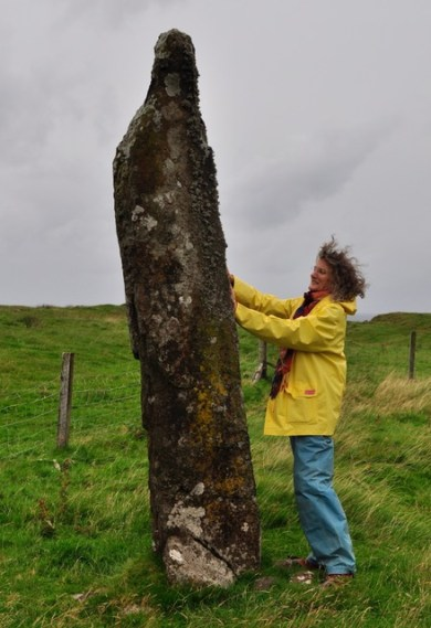 A woman in a yellow rain jacket with two hands on a standing stone.