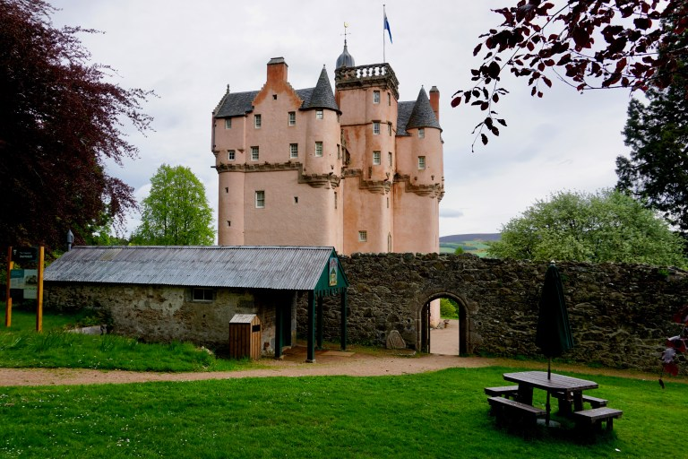 Craigievar Castle behind the remains of a stone courtyard wall.