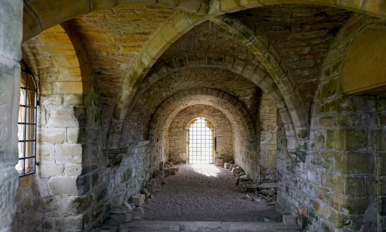 An arched ceiling and stonework inside Kinloss Abbey.