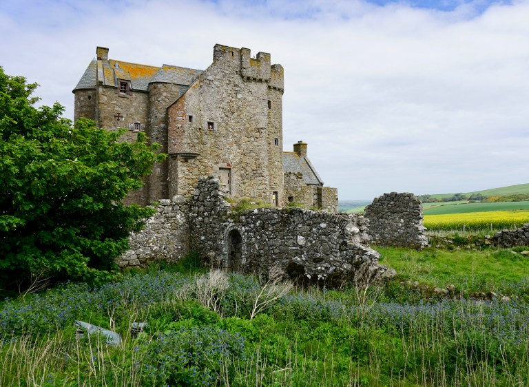 A ruined castle wall and Inchdrewer Castle.