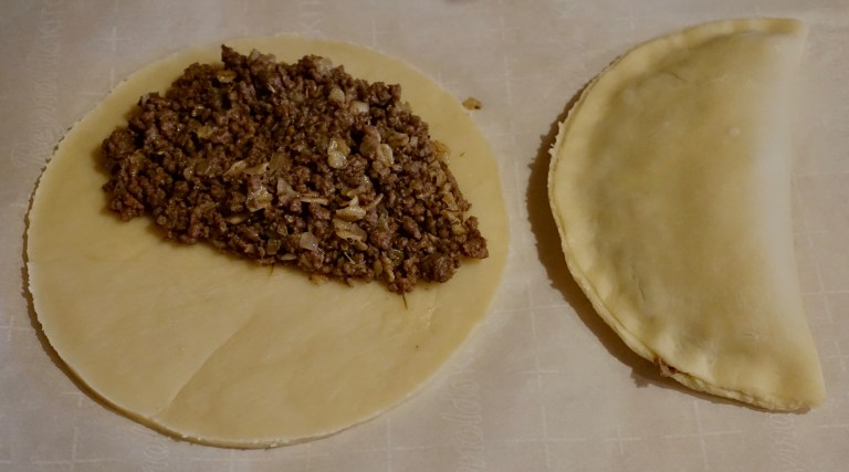 A circle of dough filled with bridie meat mixture and a bridie that has been filled and sealed.