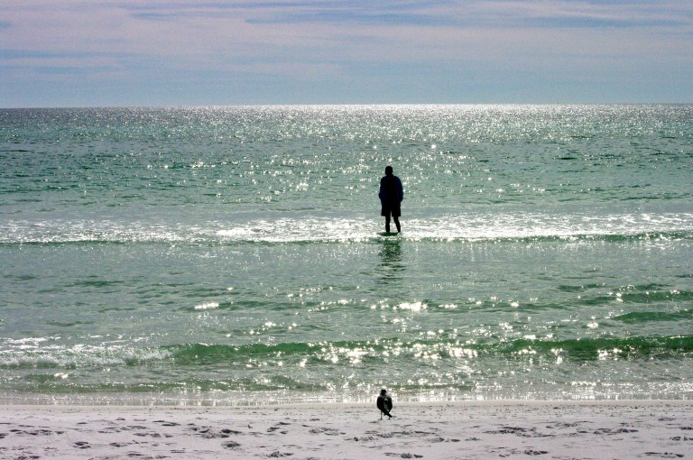 A man standing on a sand shelf in the sparkling waters of the Gulf of Mexico.