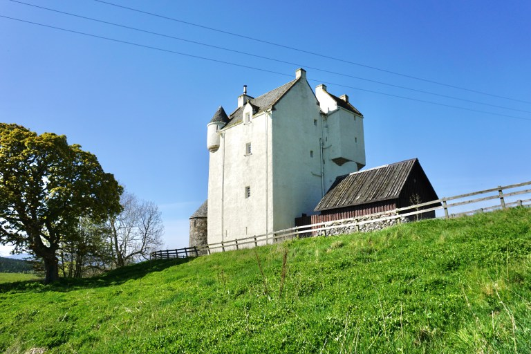Muckrach Castle at the top of a sloped hill under a bright blue sky.