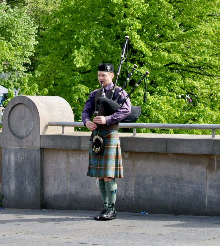 A Scotsman in a kilt playing the bagpipes in Edinburgh, Scotland.