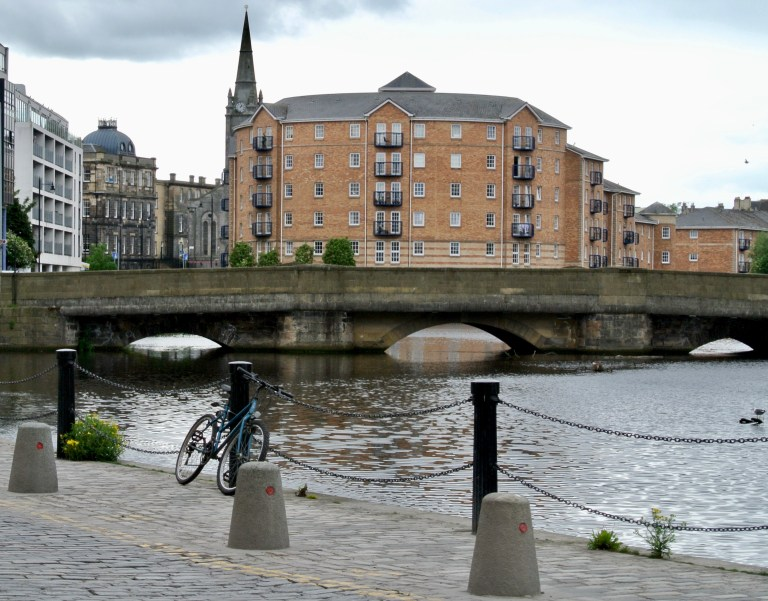 A bicycle parked on a cobbled sidewalk next to the water in Leith, Scotland.