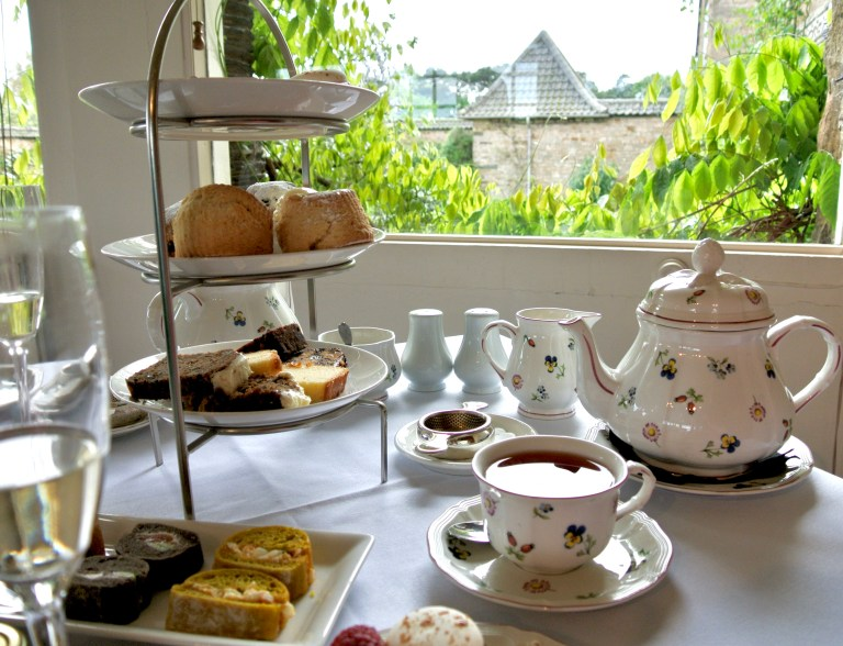 Afternoon tea; a teapot, teacups, and a tiered tray of food.