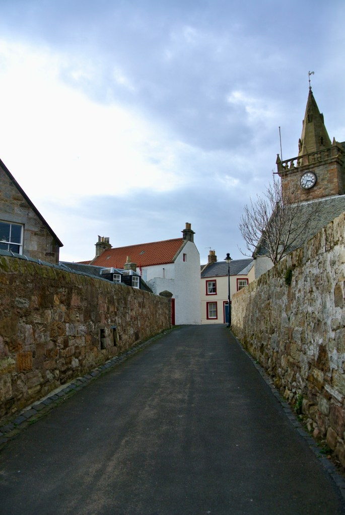 A narrow street between two stone walls in Pittenweem, Scotland.