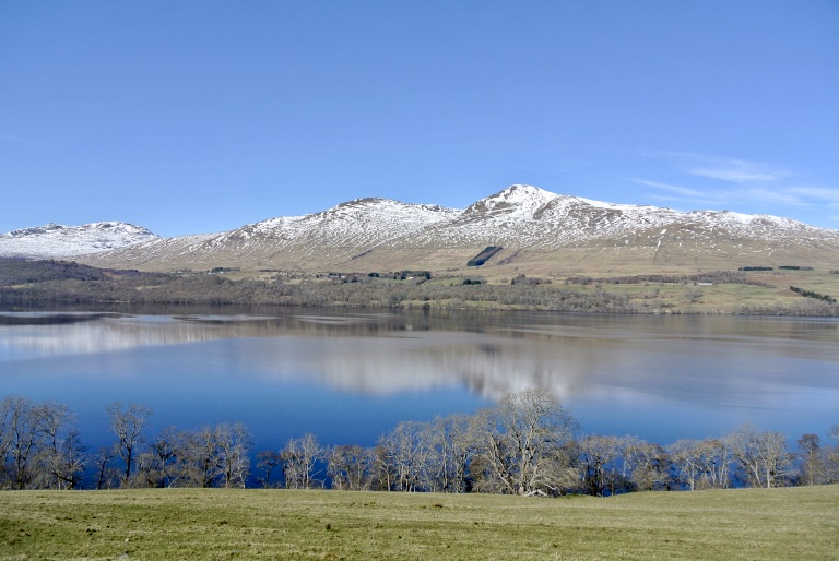 Snow covered hills reflected in still water.