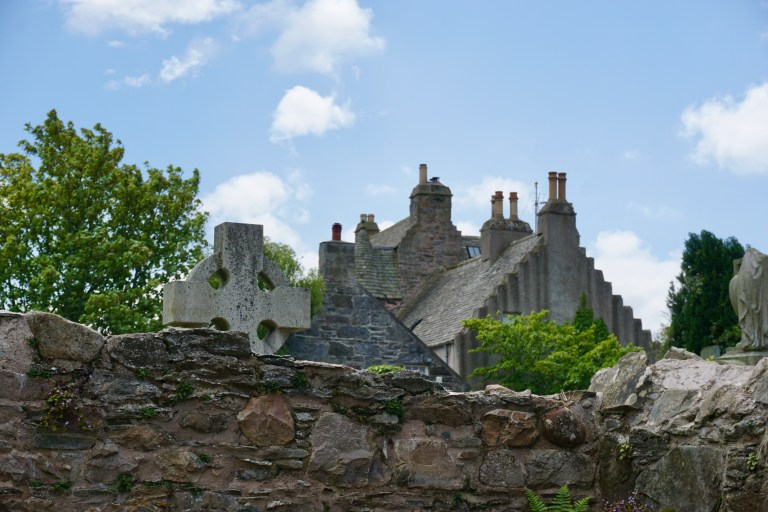 A stone wall and a celtic cross in front of Fordyce Castle.