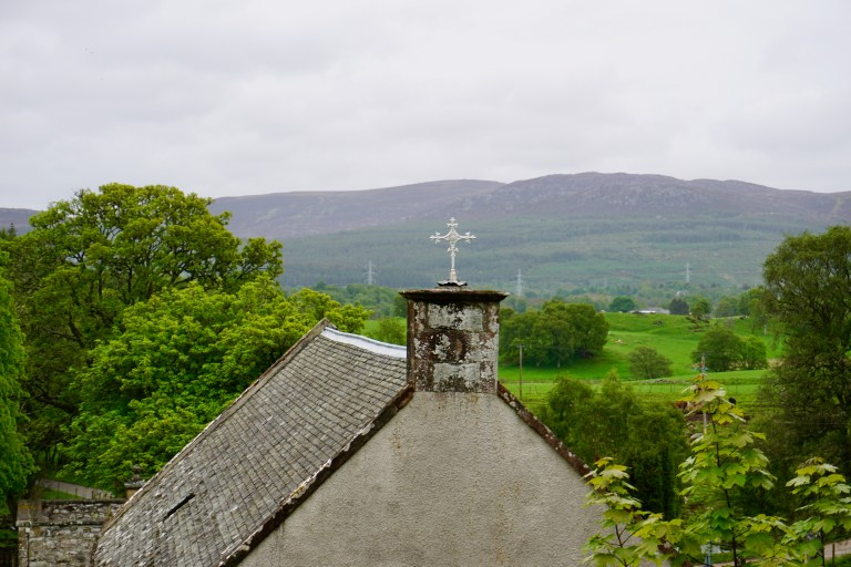 An ornate cross on the top of an old church with mountains in the background.