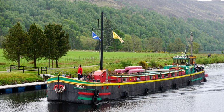 A man standing on a barge on the Caledonian Canal
