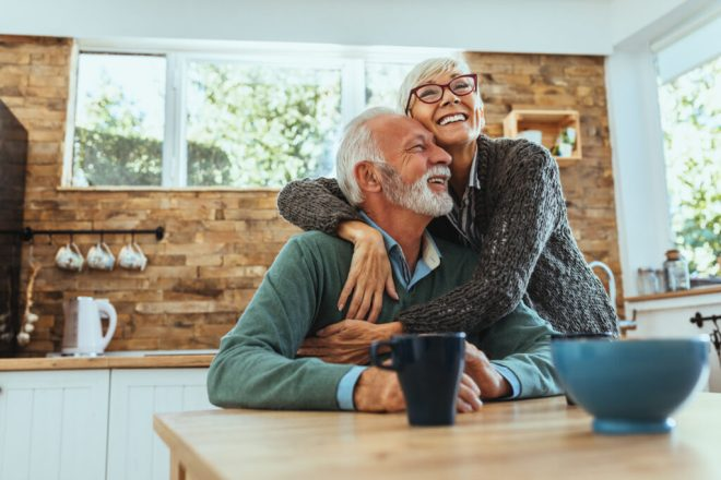 Older couple embracing in their kitchen extension