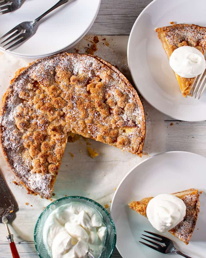 whole peach and almond tart with two slices cut out and on plates with dish of whipped cream