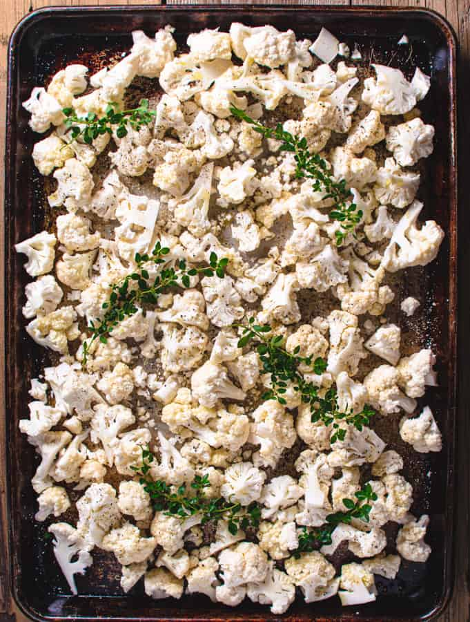 cut up cauliflower on baking tray with fresh thyme before baking
