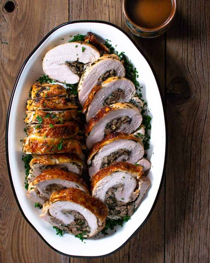 stuffed turkey breast slices on white platter with cup of sauce