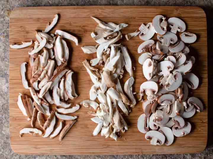oyster, shitake and cremini mushrooms sliced on a wood cutting board