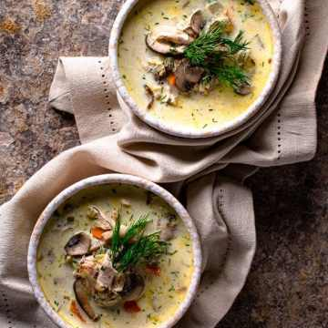 2 bowls of creamy chicken mushroom soup on a natural linen napkin garnished with fresh dill