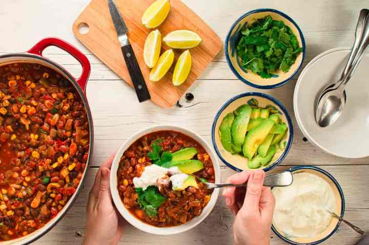 one bowl of vegetarian chili with the pot on the side. Small dishes of toppings. Avocado, cilantro and limes
