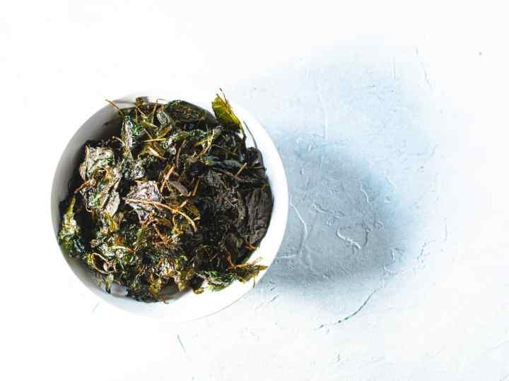 kale crisps in white bowl on light blue background