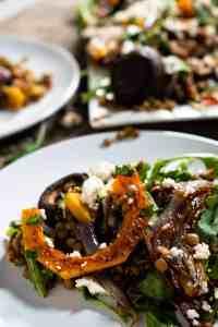 close up of warm lentil salad on white plate