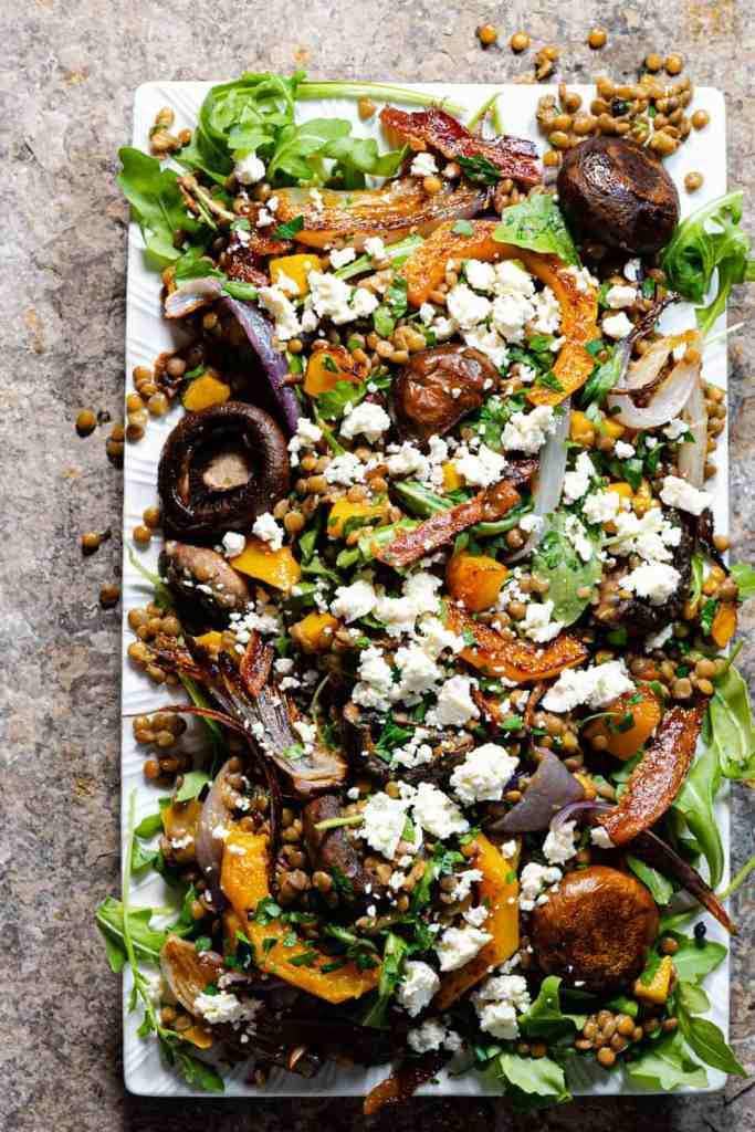 Warm lentil salad with roasted vegetables and bacon on a white platter garnished with feta cheese