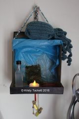 Hearth Keeper writes: This is a second shrine for Poseidon that I made from recycled materials that looks like a beach (more so on the inside).  It's not quite finished, but then what shrine is in the beginning?  On top is an octopus that I crocheted for Him.  Within is a mini alcohol bottle filled with salt water, a piece of roasted seaweed, a red plate of rosemary and sea salt, an an LED light (because having a real tealight in this space isn't space).  It's hanging by three braided yarns, each color representing Poseidon, Zeus, and Hades.  Hanging down beneath are protective bottles.  Not pictured in this photo is a dolphin charm that represents His wife, Amphitrite.  [Jo writes: YAY POSEIDON SHRINE!!!! *ahem*]