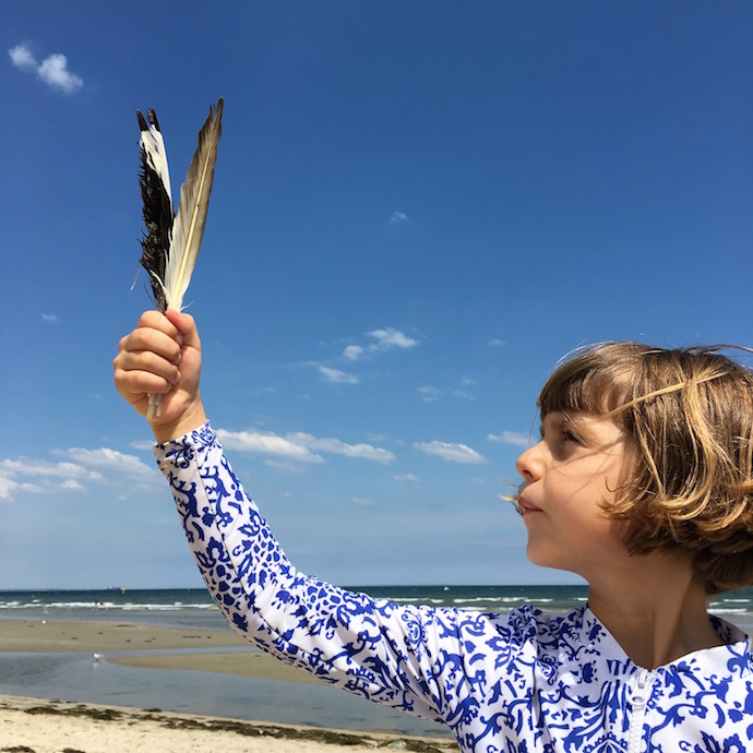 girl on beach holding feathers